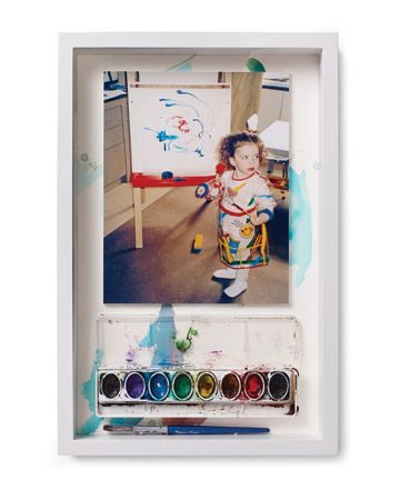To celebrate the creative process, paint-spattered watercolor set are mounted on foam board and affixed to painting. A brush rests along the bottom of the box. I love love love this idea