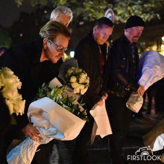 Bono and band members of U2 pay their respects and place flowers on the pavement near the scene of yesterday's Bataclan Theatre terrorist attack on November 14, 2015 in Paris, France. At least 120 people have been killed and over 200 injured, 80 of which seriously, following a series of terrorist attacks in the French capital. (Photo by Jeff J Mitchell/Getty Images)