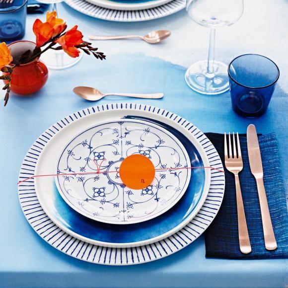 Eingedeckter Sitzplatz  mit verschiedenen blau-weißen Tellern und kupferfarbendem Besteck
