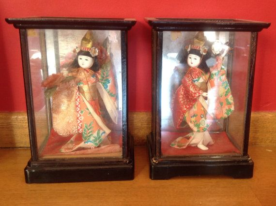 Japanese HANDMADE dolls inside cases Faces and hands are made out of porcelain and beautiful fabric uniforms . The cases are made out of wood and glass and they measure 24.50cmx17.50x7.50cm On the back there is a mirror The condition is good Ideal gift for a collector Thanks for visiting