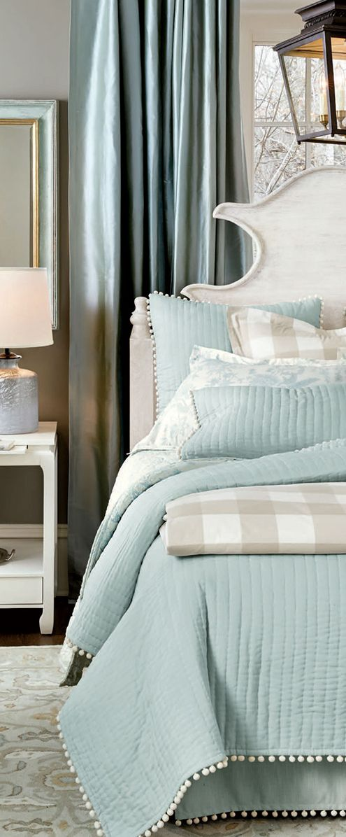A dark gray wall contrasts with pretty shades of spa blue in this bedroom.