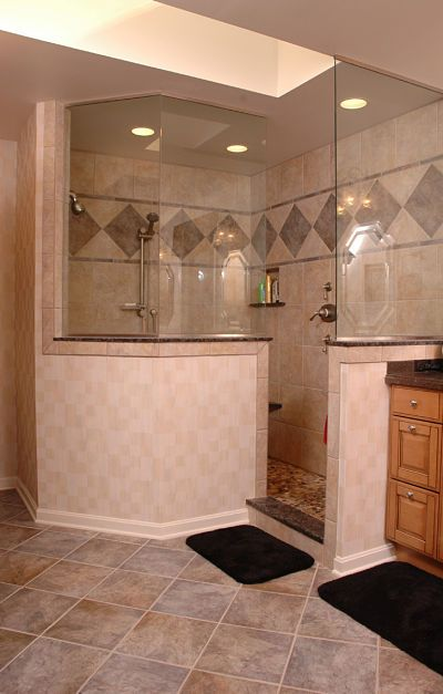A knee wall creates privacy in a doorless walk-in shower with a glass enclosure. By Neal's Design Remodel.