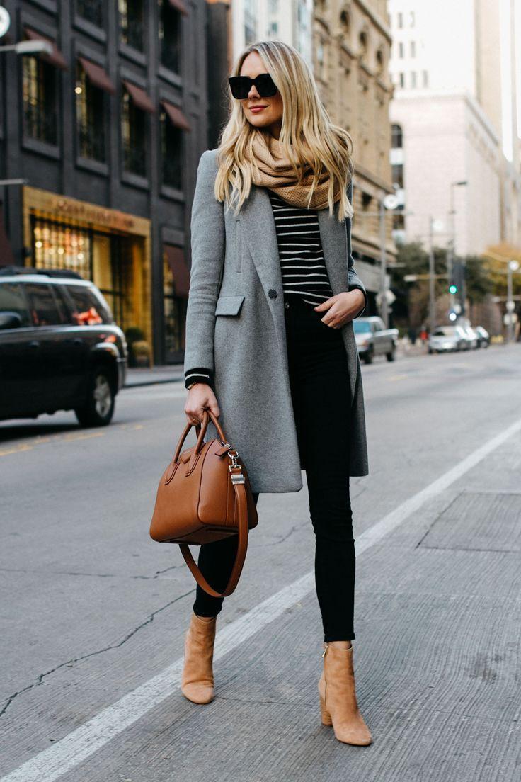 Ein elegantes Herbstoutfit aus einem grauen Wollmantel, gestreiftem Oberteil, schwarzer Hose, beigen Stiefeln, Schal und Tasche.
