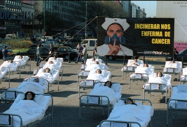 """Octubre 2001: Cuarenta activistas de Greenpeace montaron una escenografía en el Obelisco en la que aparecían corno enfermos afectados por las emisiones procedentes de la incineración de residuos hospitalarios bajo un cartel con la leyenda """"Incinerar nos enferma de cáncer"""". Luego de esta campaña, se prohibió la incineración de residuos patógenos en la Ciudad.    © Greenpeace"""