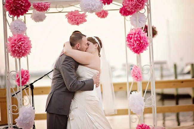 DIY Paper Pom Wedding Arch: They exchanged vows below a gorgeous wedding arch decorated with large handmade paper poms made from tissue paper in white and varying shades of pink. Nautical Wedding in Navy Blue & Pink | Confetti Daydreams