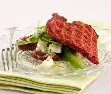 Ett charmigt och snabblagat recept på rosmarindoftande rödbetsvåffla med fetaost. Du gör det av bland annat rödbeta, ägg, mjöl, mjölk, fetaost och ruccola. De färgglada våfflorna passar utmärkt att servera som förrätt!