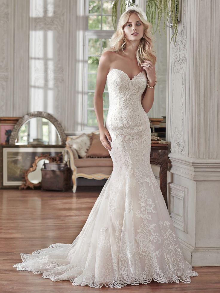 Maggie Sottero - ROSAMUND, Lovely in lace, this fit and flare lace wedding dress is the epitome of beauty with bold lace appliqués laying atop tulle, cascading to a subtly flared skirt. Finished with sweetheart neckline and corset closure. Detachable lace cap-sleeves sold separately.