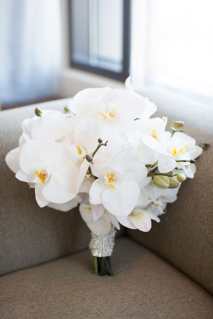 Courtney wanted all the flowers that decorated the day to be white, including her bridal bouquet filled solely with white orchids. From An Elegant, Modern Wedding at San Francisco Ferry Building in San Francisco, California
