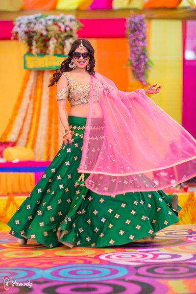 Sangeet Lehengas - Bride in a Green Lehenga with Golden Embroidery and a Pink Net Dupatta | WedMeGood Photo by: Picsurely Films #wedmegood #indianbride #indianwedding #lehenga #sangeetlehenga #twirling #coldshoulder