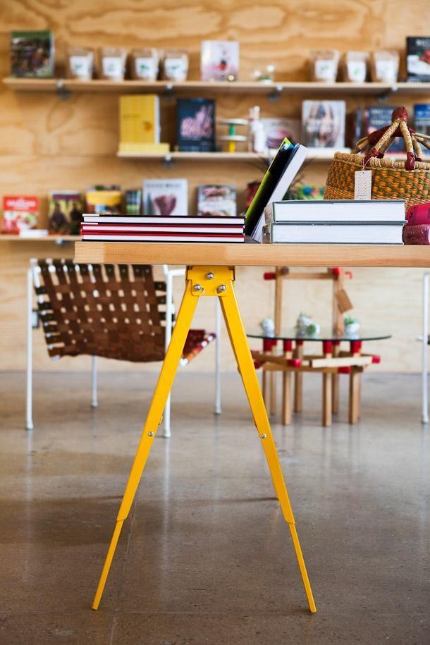 Yellow trestle legs work table + display shelves at Poketo: Remodelista