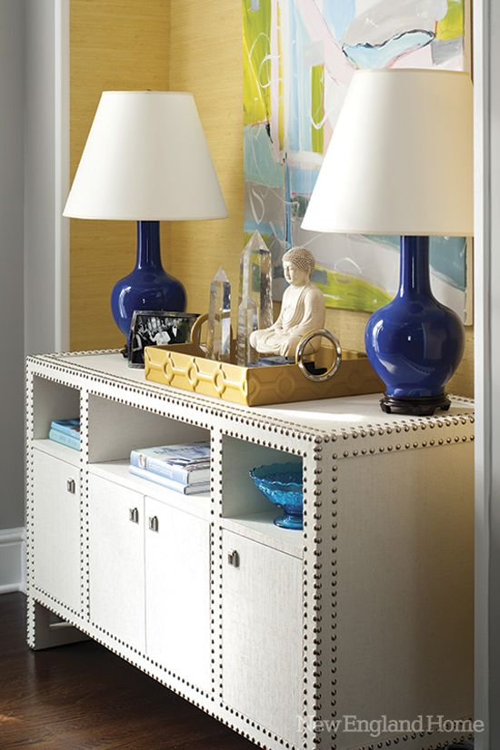 I love the colors and textures here! Shiny blue lamps, yellow grasscloth wallpaper, the green in the picture, the nailheads, the crystals....beautifully eclectic!
