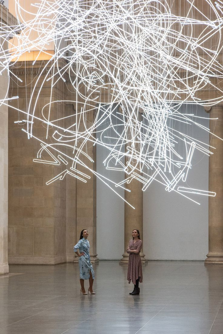 Suspended from the ceiling of Tate Britain's Duveen Galleries is Welsh artist Cerith Wyn Evans' latest installation, over a mile of bright neon lighting broken into abstract lines and monumental curves. The piece, Forms in Space... by Light (in Time), changes with perspective, each of the wo