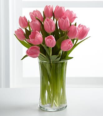 Tulips, the quintessential springtime flower!  Two bundles of pink tulips in a glass vase by the door for Easter.