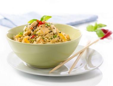 Für den gebratenen Eierreis mit Hühnerbrust und Gemüse die Hühnerbrust in kleine Stücke schneiden, die Frühlingszwiebeln in dünne Ringe. Das Gemüse