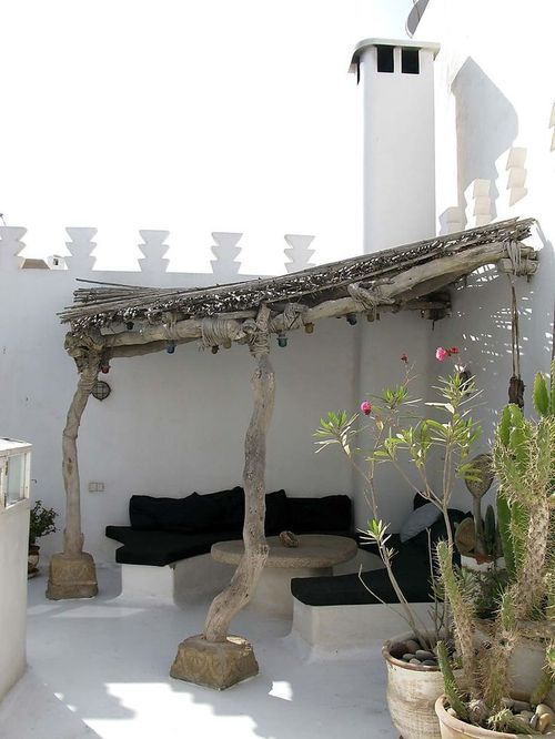 Lovely rustic look - shady seating in a hot white courtyard.