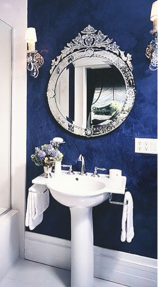 Bold wallpaper and Venetian Mirror work well to create a dramatic powder room!