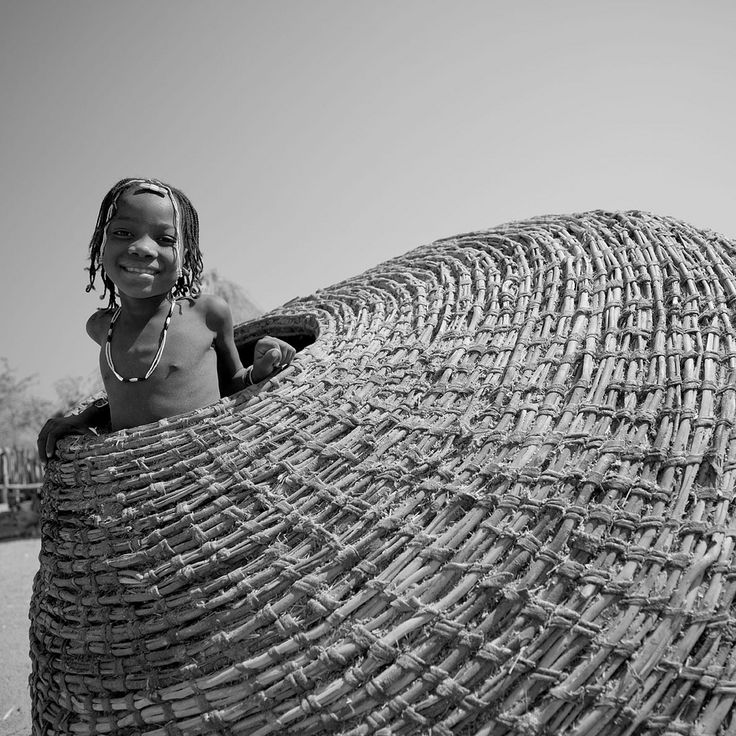 Africa   Mudimba tribe kid in a giant basket.  These baskets are used for storing grain.  South Angola   © Eric Lafforgue