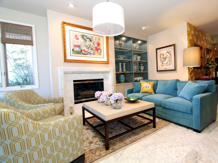 A bright blue sofa, pair of orange-patterned chairs and a neutral square coffee table fill this white living room with color. A white marble fireplace, white drum chandelier and lit built-in lit bookcases complete the space.