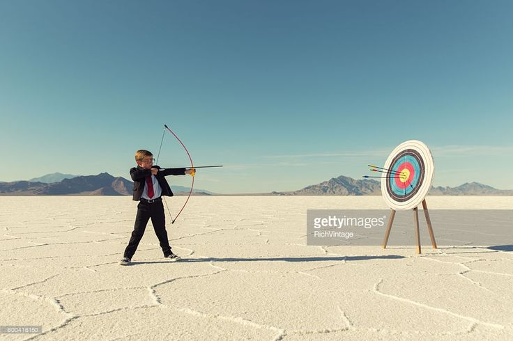 Stock Photo : Young Boy Businessman Shoots Arrows at Target