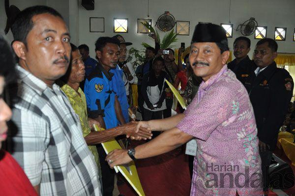 PENGHARGAAN-Plt Sekdakab Langkat H Indra Salahuddin memberikan penghargaan kepada salah satu penerima program bedah rumah pada acara Pencana...