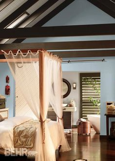 You don't have to be next to the beach to create a relaxing oasis—instead create a serene, calming bedroom with a soft color palette. A cooling blue paint shade, such as BEHR Sky Light View, paired with exposed wood beams will help create a master bedroom retreat in your home.