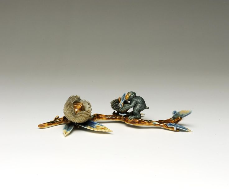 Paperweight of porcelain, in the form of a grey monkey on a chestnut branch: Japan, 19th century.