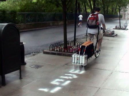 Bicicleta que lleva acoplado en la parte trasera unos inyectores de tinta que van pintando palabras en el suelo.