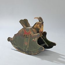 A Norwegian rocking horse of painted wood in the form of a mountain goat.