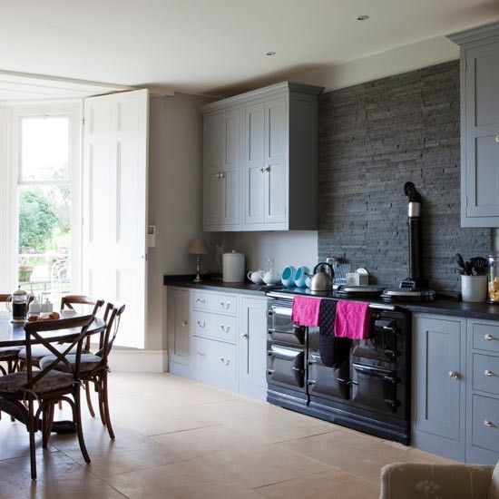 The huge Aga warms the large room and is given a contemporary edge with the addition of a striking slate splashback. Spots of hot pink are added here and there to brighten up the look