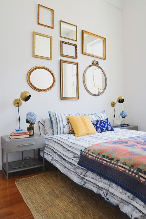 """""""For the bedroom, we created a focal wall of vintage gold mirrors and brass wall sconces above the low platform bed to create drama and height. The mirrors are all vintage which makes the space unique. I spent hours with Matt and Allie in a thrift store called Junk in Williamsburg to find the perfect mix of shapes and sizes. The vintage wall behind the bed was one of my favorite parts of the project. If only, every client I work with had ceilings so high!"""""""