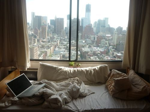 Bed pushed up against window with a nice view
