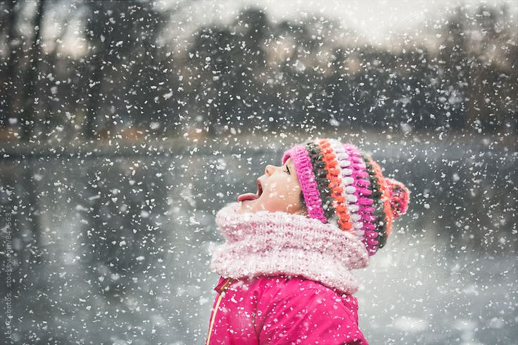 Cute little girl sticking her tongue out and catching snowflakes by Lea Csontos