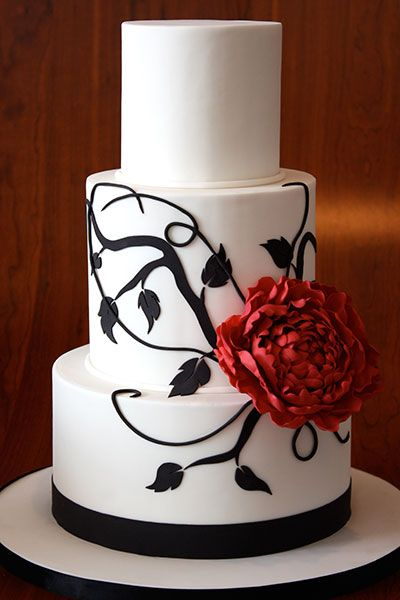 Fondant branches with a single flower make a bold impact.Cake by Elegantly Iced
