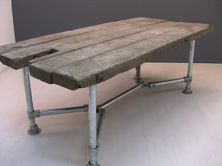 Reclaimed wood table with V base made of Kee Klamp and pipe.