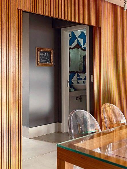 O painel ripado de freijó separa a área social da cozinha e do lavabo. Projeto da arquiteta Gabriela Marques                                                                                                                                                     Mais