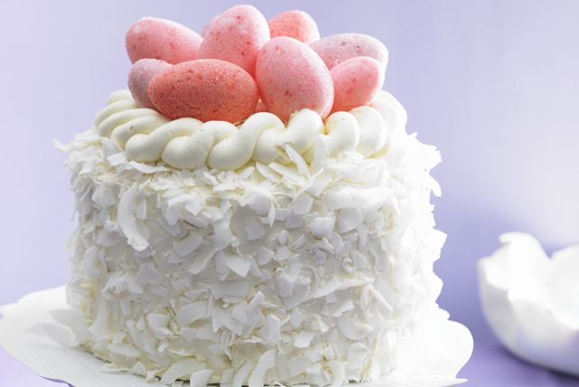 Looking for a yummy Easter cake recipe?  Our Easter Cake with Coconut is a wonderful choice! This recipe features a white cake filled with raspberry jam, frosted with a simple cream cheese frosting, garnished with shaved coconut and topped with pretty pink candy eggs.