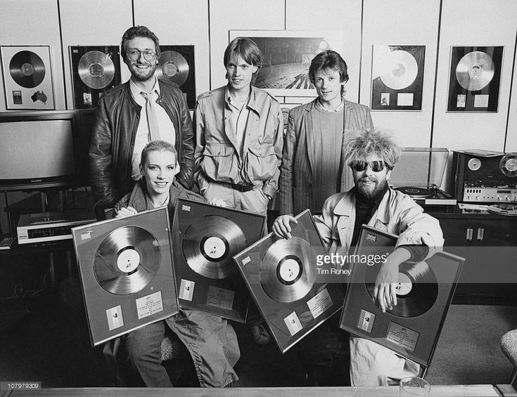 British pop duo Annie Lennox (foreground, left) and David A. Stewart (right) of the Eurythmics, at the RCA Records offices, with the gold and platinum discs awarded for sales of their album 'Sweet Dreams (Are Made of This)', January 1984.