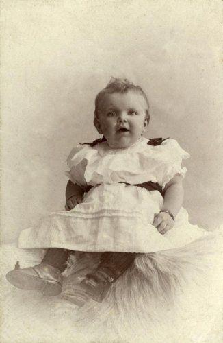 Portretten, studioportretten Nederland. Studioportret van een peuter [meisje] in een witte jurk, versierd met donkere lintjes. Zij is gezeten op een schapenvel. Baarn, tussen 1897 en 1912. [Zie ook: SFA003009316]