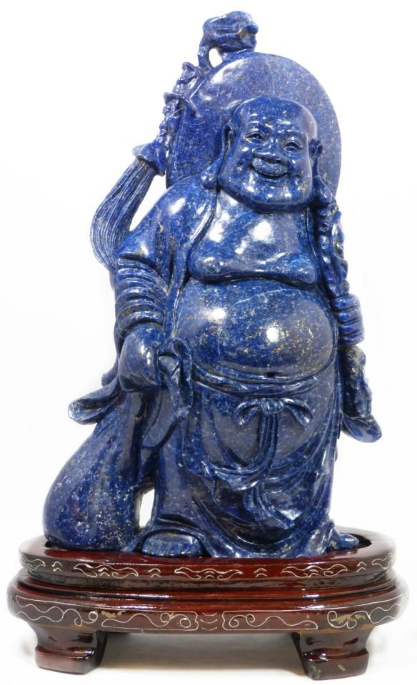 """Stunning hand carved solid gem quality lapis lazuli Buddha figure. He is depicted standing with staff in left hand and bag in right. Measures 12"""" height x 7"""" width + 2 1/2"""" height (30.54cm x 17.7cm + 6.3cm)."""