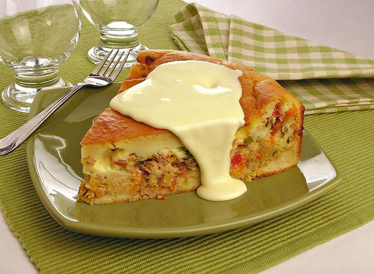 Um pedaço triangular da torta de frango e palmito está sobre um prato verde e um pouco de Catupiry® está escorrendo sobre o pedaço