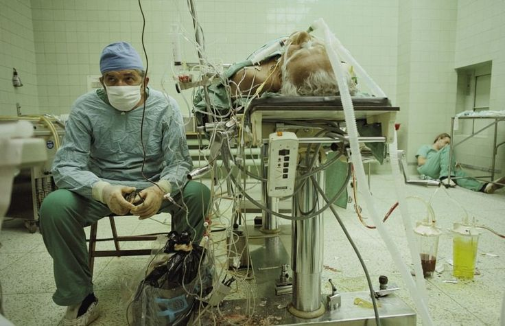 Dr. Religa monitors his patient's vitals after a 23 hour long heart transplant surgery. His assistant is sleeping in the corner. [1987]