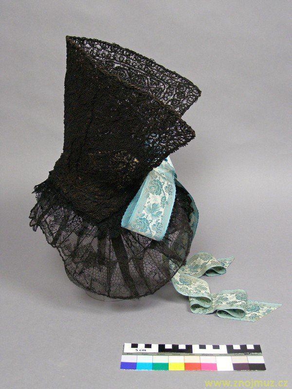 Čepec černý krepina, zřejmě frivolitková krajka, paličkovaná černá krajka, hedvábná stuha s vytkávanými světlemodrými květy, Starý Šaldorf.