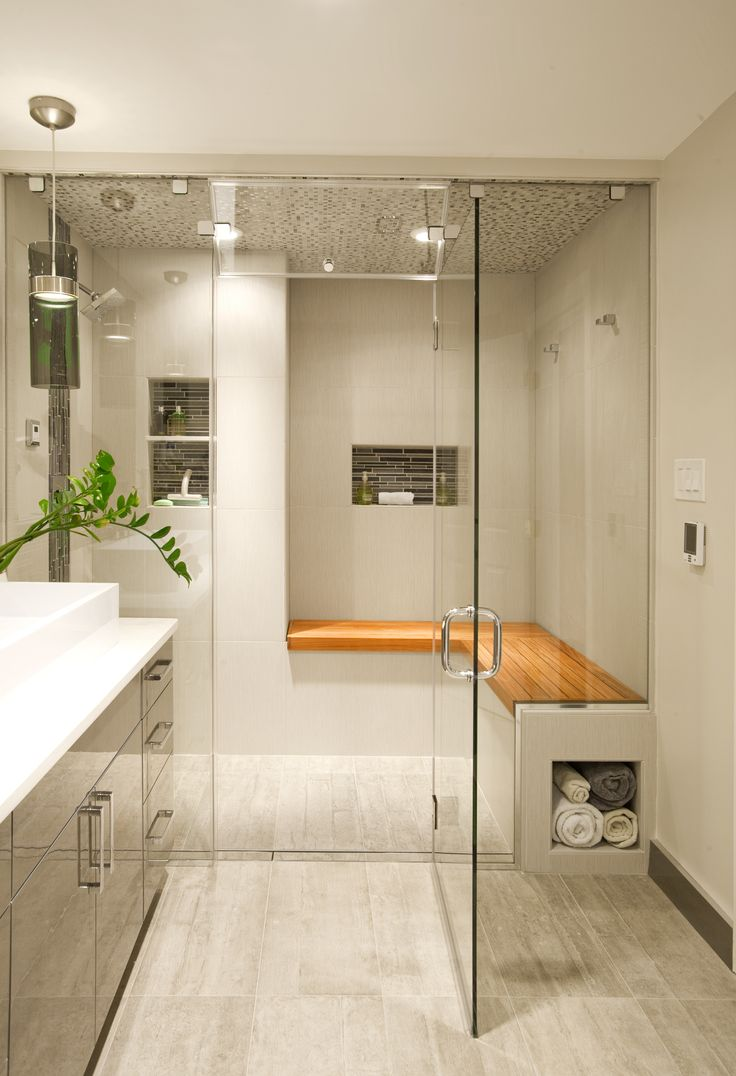 The entry into this contemporary steam shower in Bryn Mawr, PA is featuring teak wood bench seating and built in tiled shower alcoves. As an added feature, a custom  exterior towel storage was built into side profile of shower seat. Full mosaic tile ceiling with LED lighting and radiant heated floors.