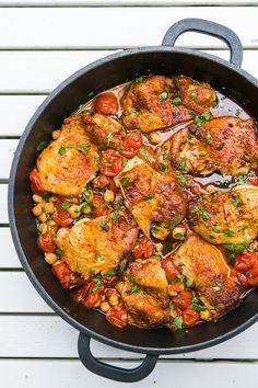 Všechny ingredience v podstatě jen smícháte a pak už jen čekáte, až vám trouba vrátí tenhle voňavý výsledek; 4 vykostěná kuřecí stehna s kůží, 2 hrnky keříčkových rajčat (500 g), 1 plechovku cizrny nebo bílých fazolí (400 g), 4 lžíce olivového oleje, 4 stroužky česneku, lžíci sladké papriky (půlku můžete nahradit uzenou paprikou), ½ lžičky pálivé papriky, lžičku drceného římského kmínu, lžičku soli, pepř, hladkolistou petržel nebo koriandrmä