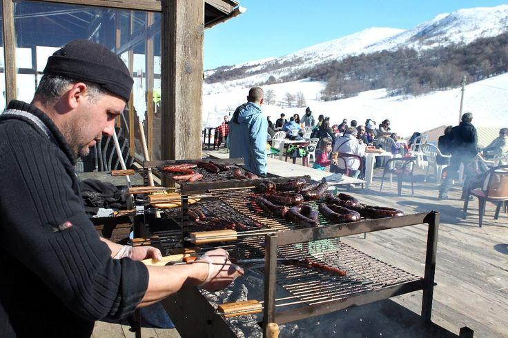 Un homme prépare un plat typique corse dans un restaurant de la station de sports d'hiver Val d'Ese en Corse du sud. - Pascal Pochard-Casabianca - AFP