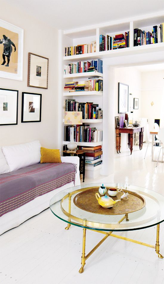 Small Space, Small Library, done very Well. The Round Brass Footed Coffee Table and the Addition of a Well Worn Antique Oriental Rug would Define the Space, and Create the Illusion of a True 'Room'. Very Handsome.