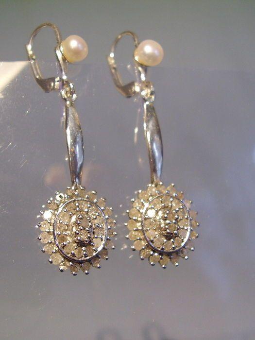 Grote diamantoorringen diamanten 102 ct 8/8 W-PI  De oorbellen zijn gemaakt van zilver 925 en dienovereenkomstig zijn hallmarked. De oorhaken zijn met echte witte gekweekte zoetwaterparels onder die flexibele Hangers deze zijn volledig ingesteld met ronde gefacetteerde diamanten op 3 niveaus van ca. 102 ct in totaal.De diamanten zijn Wesselton evenals Piqué.Earring lengte 45 cm breedte 1.25 cmDiameter van de gecultiveerde parels 45 mmDiamond ovalen 13.4 x 12.4 mmgewicht 59 g.Zeer goed…