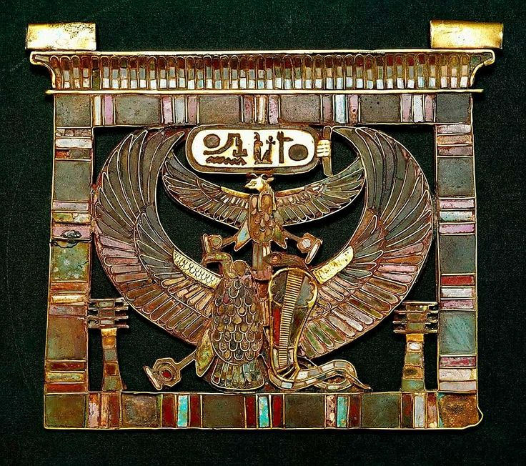 Pectoral bearing the name of Ramesses II (electrum)  Nekhbet and Wadjet, goddesses of Upper and Lower Egypt, stand side by side within the frame in the form of a temple pylon topped by a grooved cornice. They share a single set of outspread wings. A ram-headed bird over them, also with outstretched wings, is a form of the sun god Ra. Ramesses II's throne name is written in a cartouche above what is already a dense composition. Finally, two djed pillars fill in the lower corners of the…