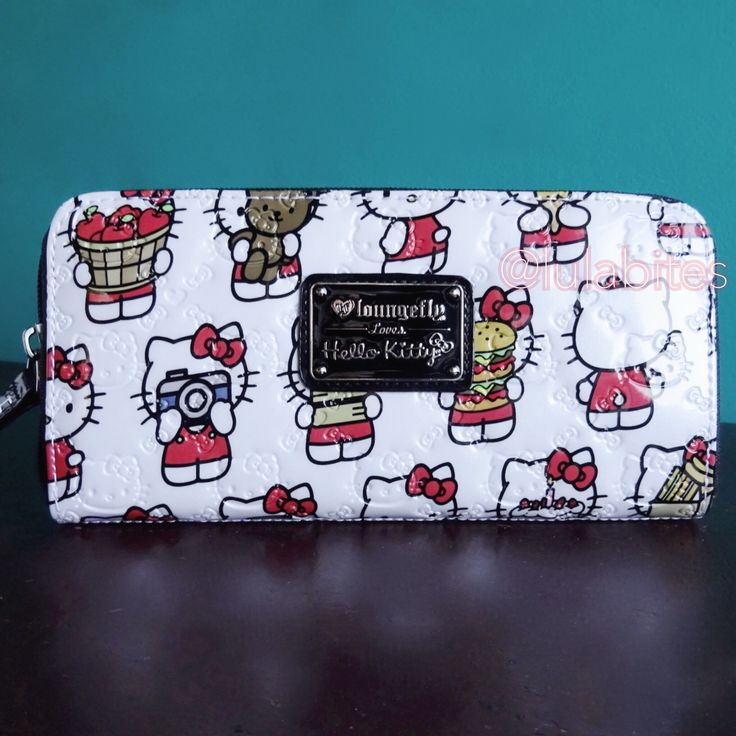 """Hello Kitty foodie wallet design from Loungefly x Hello Kitty. Comes in faux patent leather material with zip around zipper closure. Matching bag available on separate listing. MEASUREMENTS: W: 8"""" X D"""