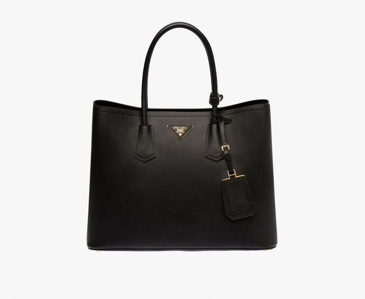Saffiano Cuir leather tote Double leather handle Detachable adjustable leather shoulder strap Steel hardware Metal lettering logo on leather triangle Snap closure on sides One inside flap pocket Nappa leather lining